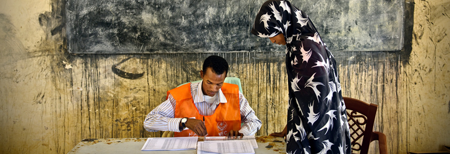 A man verifies a woman's registration as she votes in Sudan