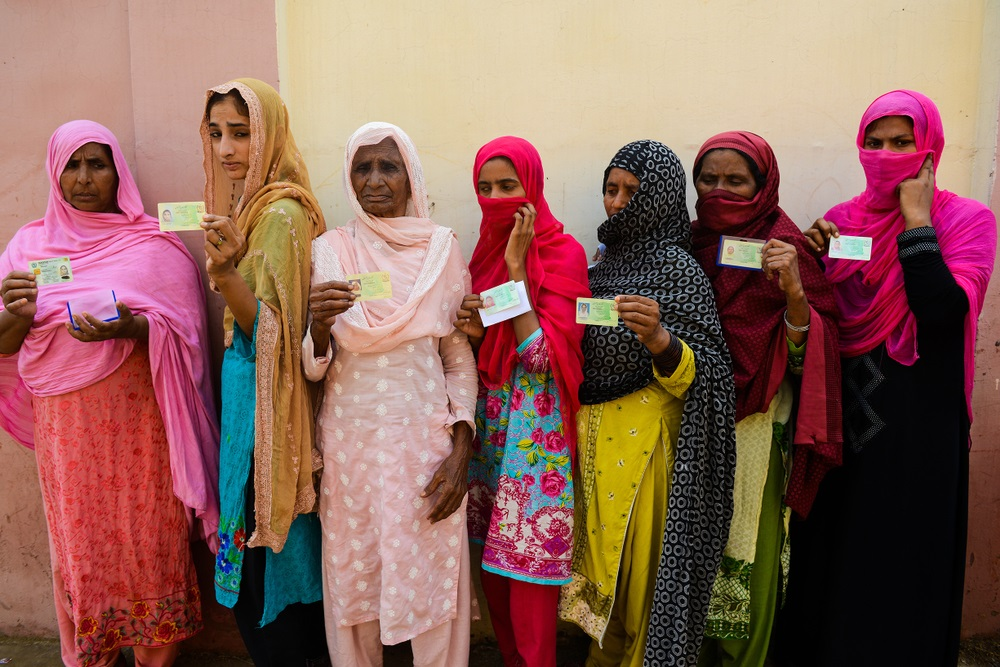Pakistani women show their voting cards stand as they wait to cast their vote outside a polling station during general election in Lahore on July 25, 2018