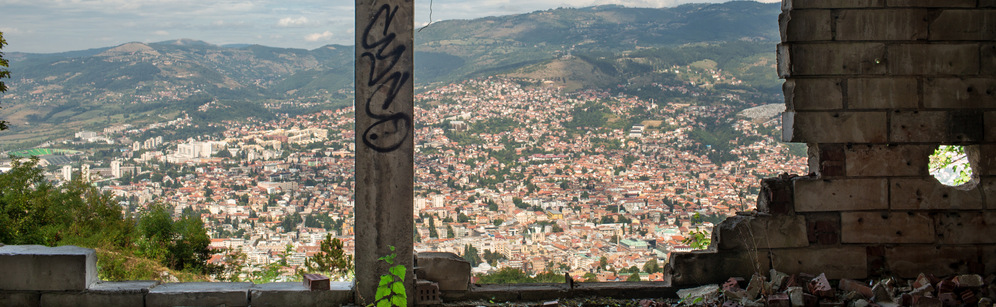 Panoramic view of Sarajevo, Bosnia and Herzegovina, seen through a bombed-out building