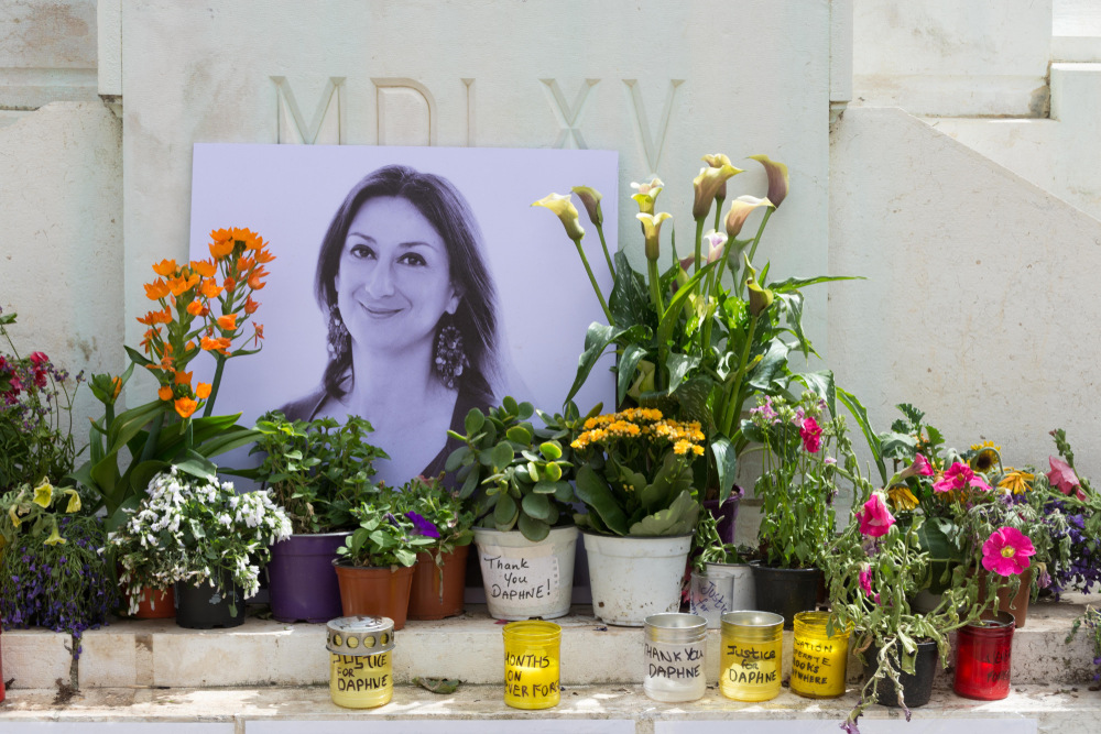 Candles, flowers and a photograph make up a memorial to the murdered journalist Daphne Caruana Galizia in Valletta, Malta