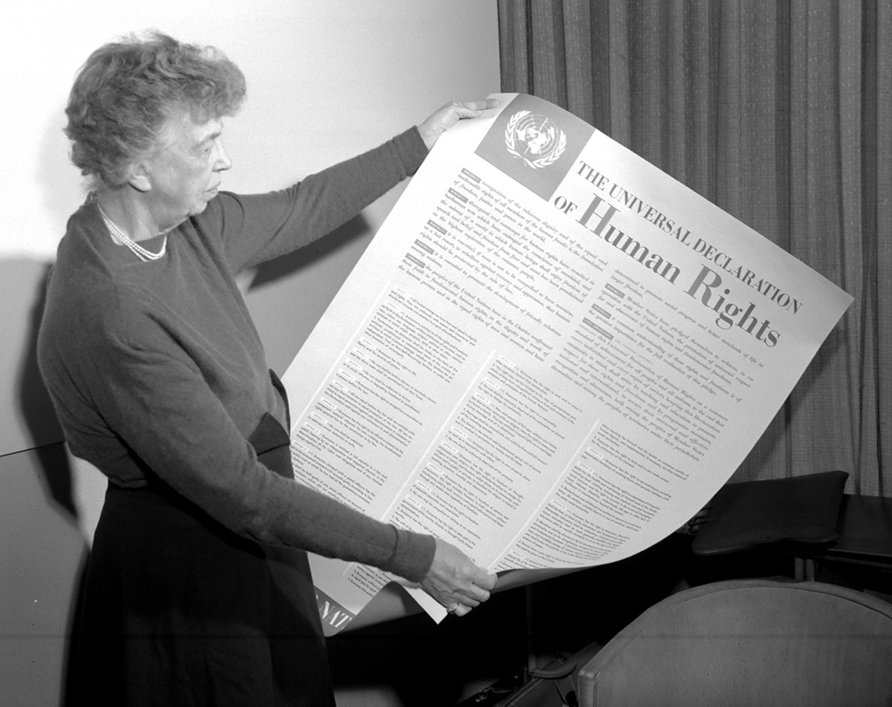 Old black and white photo of Eleanor Roosevelt holding the Universal Declaration of Human Rights in November 1949
