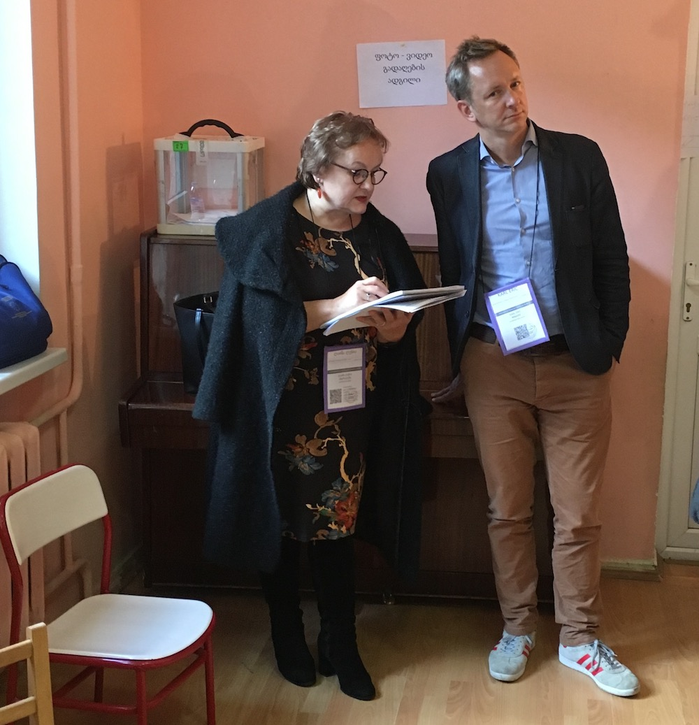 Two election observers from the European Parliament stand in the corner of a school room in Georgia and take notes on the ballot