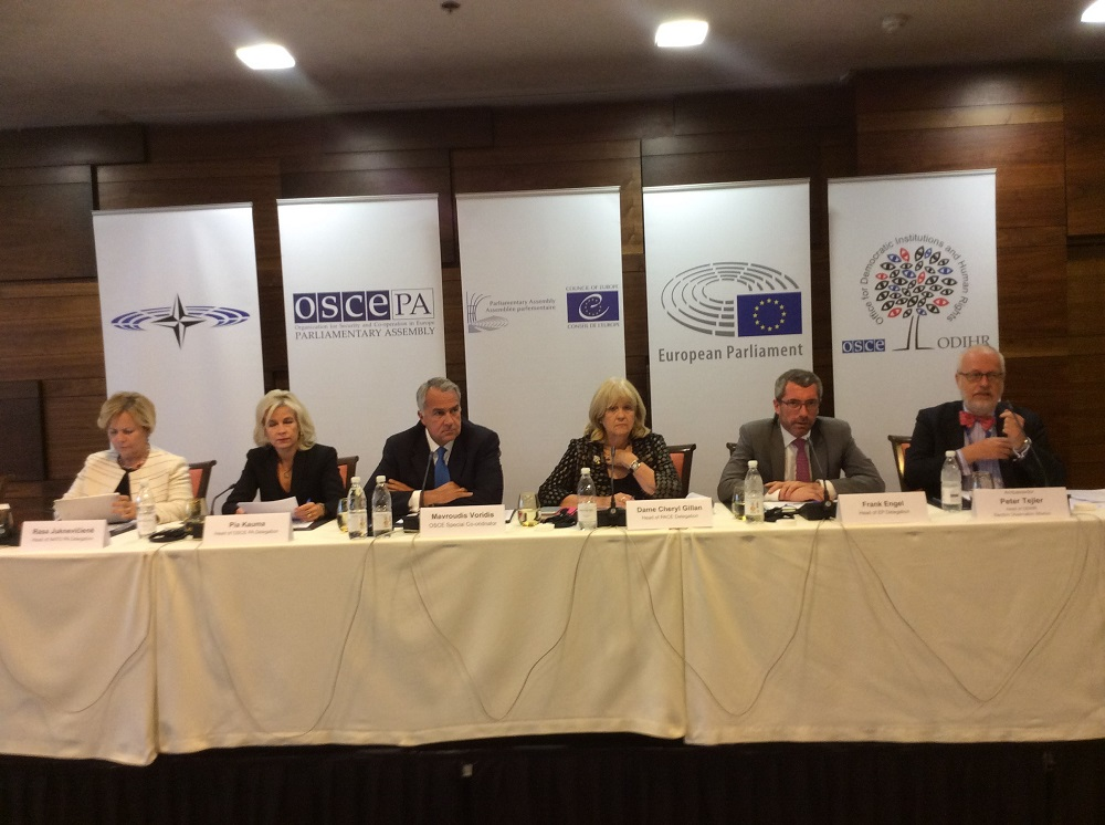 Six election observers sit at a podium to deliver their prelimary findings on the 2018 elections in Bosnia and Herzegovina