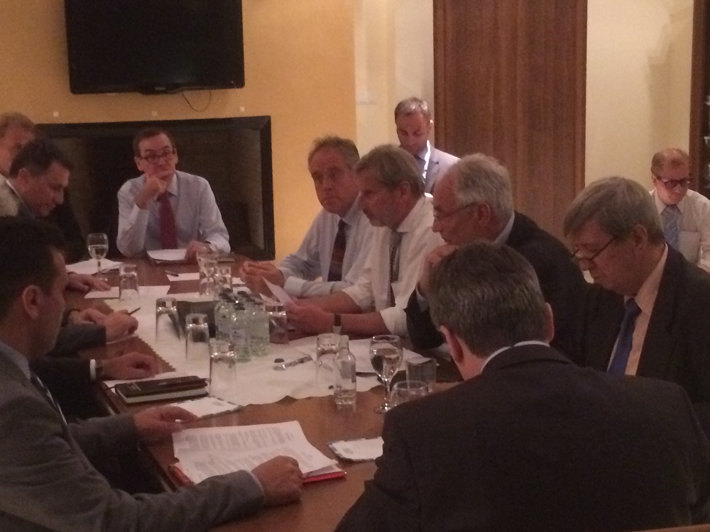 MEPs Eduard Kukan, Richard Howitt and Ivo Vajgl join European Commissioner Johannes Hahn and other negotiators seated around a table during the session in Skopje